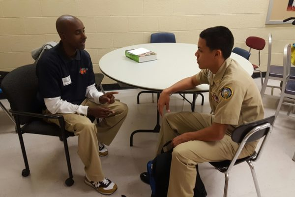 Picture of Gerald Jarmon talking with a young man in uniform
